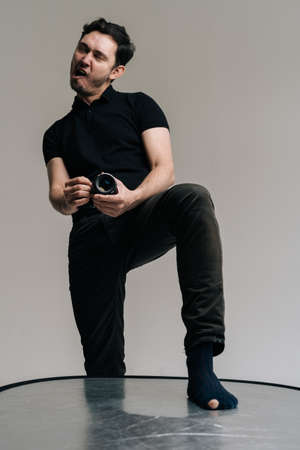 Photographer man holds digital camera in hands and takes picture with joking expression of his face. Photographer in holey socks.