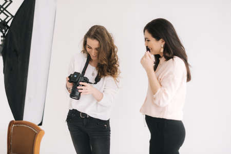 Woman photographer and female model together looking at made photo and talking,smiling, white background. Concept of creative work in photo studio, backstage job.