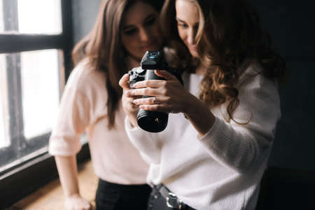 Model and female photographer looking at made photo and smiling in studio. Concept of creative work in photo studio, backstage job.