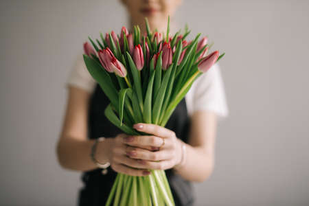 Middle shot portrait of smiling woman florist holding bouquet of flowers on white background. Concept of working with flowers, floral business.