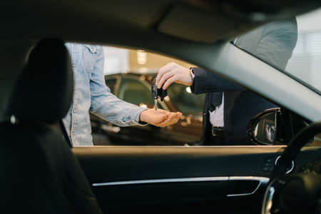 Close-up of car salesman handing over keys for new car to young man buyer in auto dealership, view from interior of car. Concept of choosing and buying new car at showroom. Standard-Bild