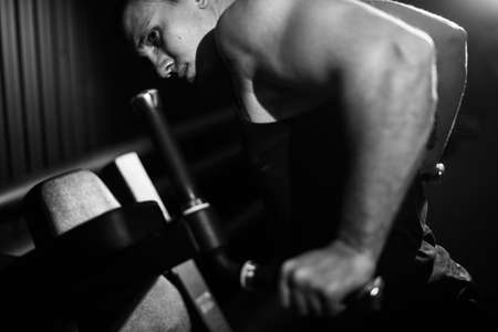 Muscular strong man with perfect beautiful body wearing sportswear doing push-ups on bars during sport workout training in modern gym, black and white color. Concept of healthy lifestyle. Фото со стока
