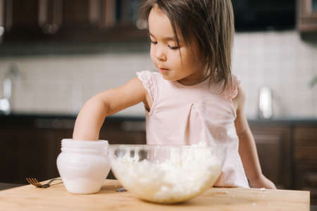 Funny beautiful little girl is taking salt from the salt cellar with fingers to add to the dough in transparent bowl for making cheesecakes at the table in kitchen with modern interior. Imagens