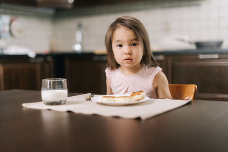 Beautiful little two-year-old girl is waiting for the meal to begin, looking at the camera.. Cheesecakes on the table in front of the child and a glass of milk for breakfast. Banco de Imagens