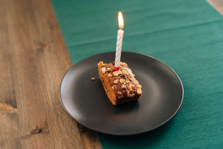 Close-up cake with burning candle in the bright room on dark plate, no people.