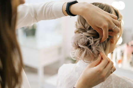 Close-up of hairdresser making hairstyle unrecognizable young blonde woman in beauty salon, back view. Concept of beauty, fashion and stylish makeup.
