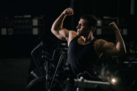 Muscular strong man with perfect beautiful body wearing sportswear standing in pose Champion in dark modern gym. Concept of healthy lifestyle. Standard-Bild