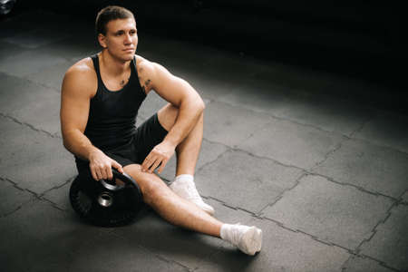 Muscular strong man with perfect beautiful body wearing sportswear sitting on the gym floor with weight from the barbell after heavy workout training in dark modern gym. Concept of healthy lifestyle. Standard-Bild