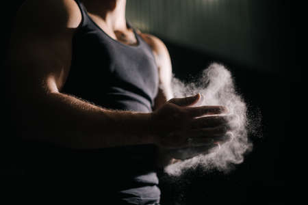 Close-up of unrecognizable strong man clapping hands with talc and preparing for workout at gym. Closeup of muscular male hands preparing for fit workout in gym with chalk magnesium carbonate.