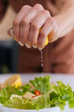 Close-up of womens hands squeezing juice from fresh yellow lemon into salad bowl with sliced vegetables. Red bell pepper, avocado, lemon on the table. Concept of healthy food lifestyle.