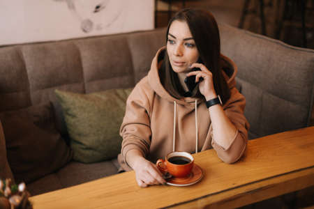 Portrait of handsome young woman in casual clothes talking on the phone at a table in a cozy cafe. Coffee cup on the table. Concept of leisure activity.