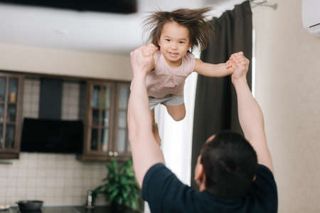 Father throws up his beloved laughing daughter in living room. Happiness beautiful little two-year-old girl is playing with his father at home during isolation. Concept of carefree childhood.
