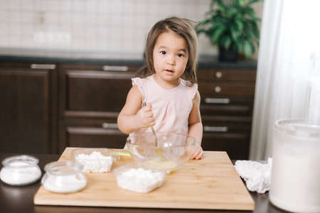 Lovely cute little girl wearing white dress is whisking eggs in mixing bowl with fork on kitchen, looking at the camera. Stock Photo