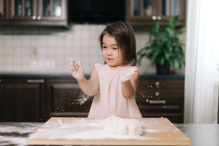 Emotional beautiful little girl is clapping hands with flour. Child is playing with flour in the kitchen while cooking homemade baked goods.