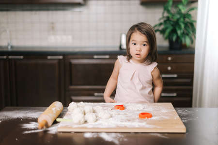 Beautiful little girl is cutting dough with form for cookies at the table in kitchen with modern interior, looking at camera.