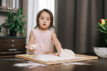 Pretty beautiful little girl is kneading dough on wooden chopping board at the table in kitchen with modern interior, looking at the camera.