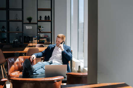 Thinking young businessman wearing fashion suit is talking on mobile phone in modern office room at the desk in modern office on background of large window, laptop on table. Concept of office working.