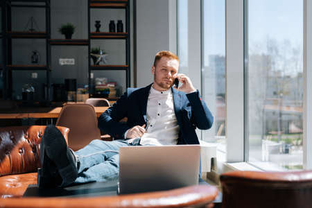 Lovely young businessman wearing fashion suit is talking on mobile phone in modern office room at the desk in modern office on background of large window, laptop on table. Concept of office working.