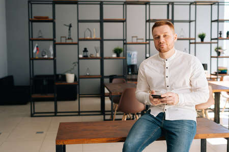 Thinking young businessman wearing fashion casual clothing is using mobile phone in modern office room sitting on wooden desk ,looking at the camera.. Concept of office working.