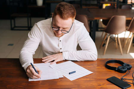 Handsome young composer wearing stylish eyeglasses is writing musical notes with pen on paper sheet music sitting at the wooden desk in modern room in home or office, headphones on table