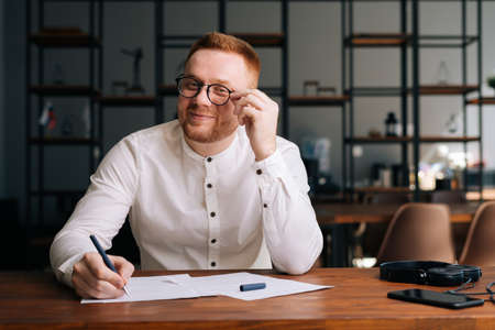 Creative happy young musician wearing stylish eyeglasses is writing note of song with pen on paper sheet music sitting at the wooden desk in modern room and looking at the camera.