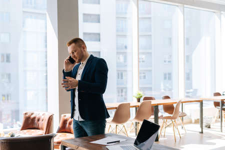 Handsome young businessman wearing fashion suit is talking on mobile phone in modern office room near wooden desk on background of large window. Concept of office working.