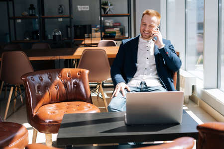 Caucasian young businessman wearing fashion suit is talking on mobile phone in modern office room at the desk in modern office on background of large window, laptop on table. Concept of office working