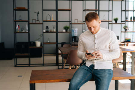 Bearded young businessman wearing fashion casual clothing is using mobile phone in modern office room sitting on wooden desk. Concept of office working.