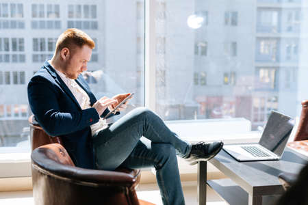 Side view of handsome young businessman wearing fashion suit is using mobile phone in modern office room at the wooden desk on background of large window, laptop on table. Concept of office working. Stock Photo