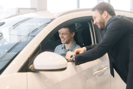 Happy young man behind the wheel of new car in auto dealership. Professional car salesman wearing business suit is telling about new car model. Concept of choosing and buying new car at showroom.