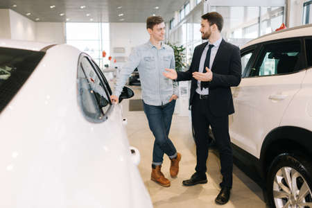 Professional car salesman wearing business suit showing new car interested buyer in auto dealership. Concept of choosing and buying new car at showroom Stock Photo