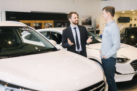 Confident car salesman wearing business suit is telling about new car model to young man wearing casual clothes in auto dealership. Concept of choosing and buying new car at showroom. Stock Photo