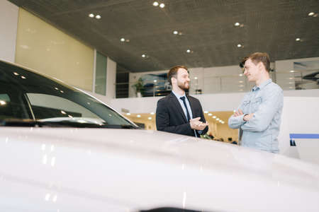 Happy smiling customer and friendly salesman wearing business suit are discussing new car in auto dealership. Concept of choosing and buying new car at showroom. Stock Photo