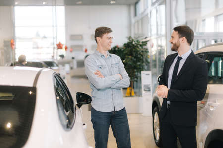 Cheerful happy man preparing to buy new car in auto dealership. Professional car salesman is telling about new car model. Concept of choosing and buying new car at showroom.