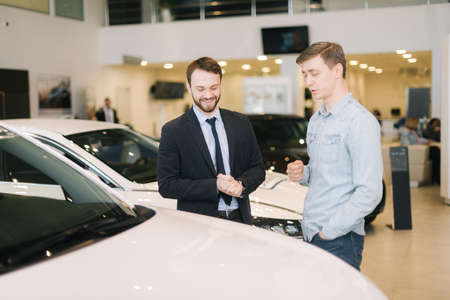Professional car salesman wearing business suit is telling interested buyer about car in auto showroom. Concept of choosing and buying new car at showroom. Stock Photo