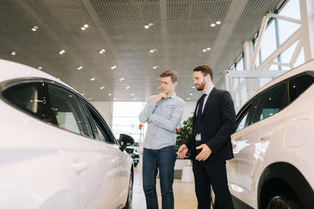 Confident male sales manager dealing with young man at the dealership. Concept of choosing and buying new car at showroom.