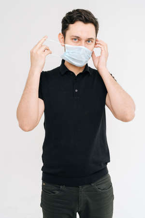 Young man with medical mask in black t-shirt. Prevention of virus infection. Concept of Coronavirus COVID-19 Pandemic.