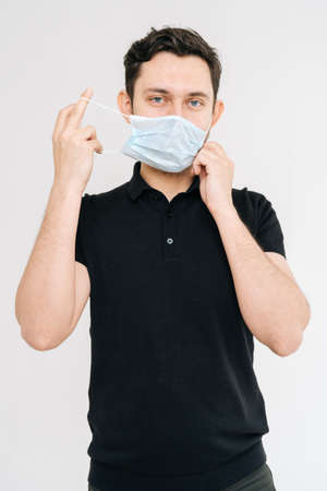 Studio portrait of young man wearing face mask and black t-shirt. Prevention of virus infection. Concept of Coronavirus COVID-19 Pandemic. Stock Photo