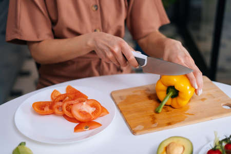 Close-up of hand of woman cutting fresh bell pepper using knife on wooden cutting board. Young woman cutting yellow bell pepper with a knife for vegetable salad. Stock Photo