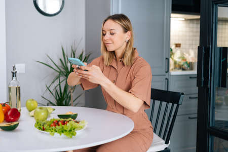 Young attractive woman photographing fresh fruits and vegetables with smartphone in kitchen with modern interior. Concept of healthy eating.