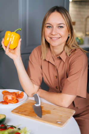 Beautiful young woman poses with yellow bell pepper at a table in kitchen with modern interior, looking at the camera. Concept of healthy eating.