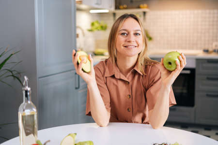 Attractive smiling woman sits at table in modern kitchen, holds in hands fresh avocado and apple. Concept of healthy eating.