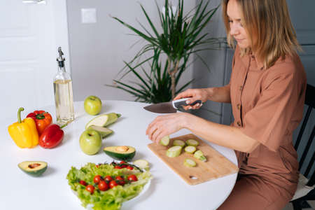 Smiling young woman cutting courgettes for preparing vegetarian salad at the table in kitchen with modern interior. Concept of healthy eating.