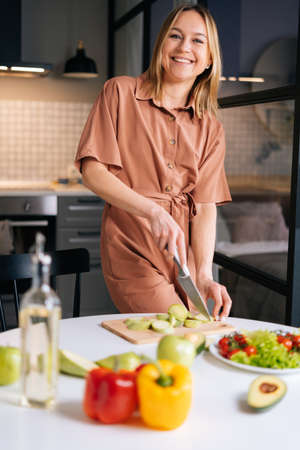 Smiling young woman slicing zucchini for preparing vegetarian salad at the table on wooden board in kitchen with modern interior, looking at the camera. Concept of healthy eating.