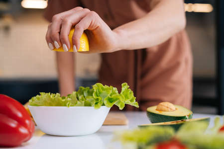 Close-up of womens hands squeezing juice from fresh yellow lemon into salad bowl with sliced vegetables. Red bell pepper, avocado, lemon on the table. Concept of healthy food lifestyle. Stock Photo