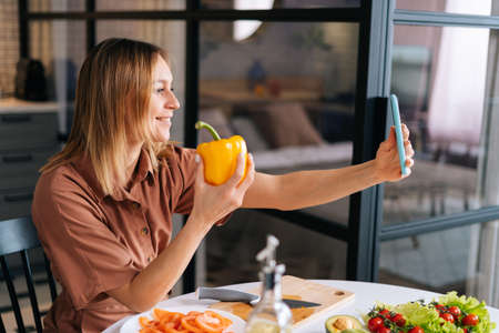 Portrait of young vegetarian woman holding yellow bell pepper in hand and takes off selfies to place pictures at social media resources. Concept of social networks.