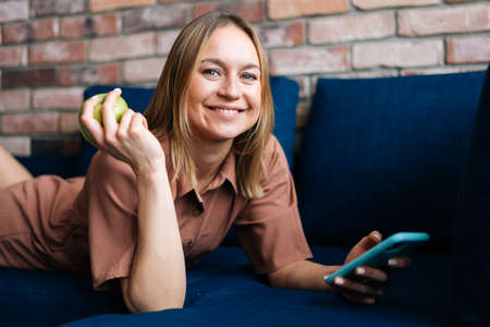 Smiling young woman lying on sofa using smartphone at home, holding green apple in her hand. Concept of communication and home coziness. Stock Photo