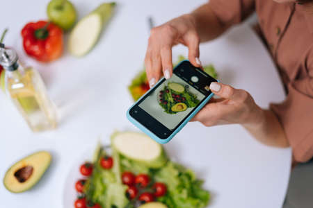 Close-up view of woman making photos vegetable salad with camera of cellphone to place pictures at social media resources. Concept of healthy eating.
