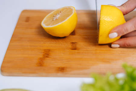 Close-up of hand of woman cutting fresh lemon using kitchen knife on wooden cutting board. Young woman cutting fresh lemon. Healthy food lifestyle concept.