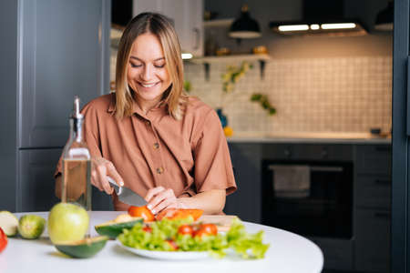 Happy smiling woman cutting fresh organic tomato with a knife for vegetable salad in modern kitchen. Smiling slim vegetarian female prepare healthy vegan dinner meal. Concept of healthy eating. Stock Photo